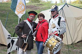 Гостья военно-исторического фестиваля Русская Троя в Севастополе фотографируется вместе с участниками мероприятия