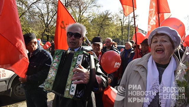 Участник шествия в честь 100-летия Великой Октябрьской социалистической революции в Симферополе поют песни под баян
