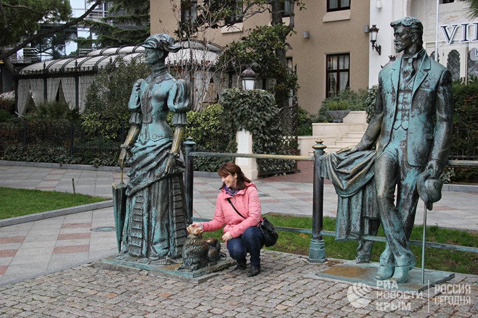 Женщина фотографируется с памятником Дама с собачкой на набережной Ялты