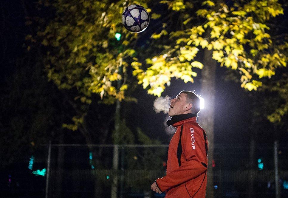 Осень в Крыму. Молодой человек играет в футбол