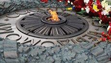 Местные жительницы возлагают цветы к Могиле Неизвестного солдата в парке Вечной славы в Киеве