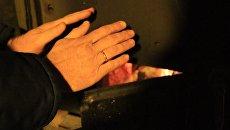 Мужчина греет руки в пункте обогрева