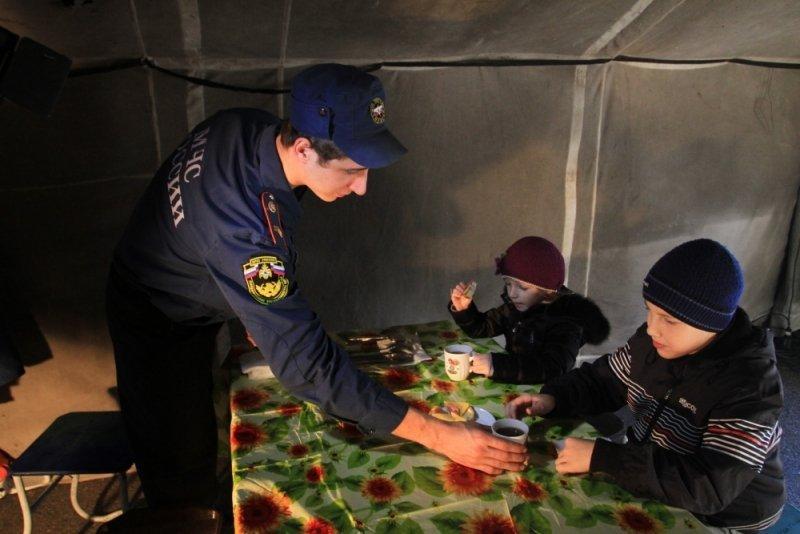 Сотрудник МЧС поит чаем детей в пункте обогрева