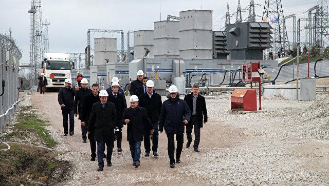 Заместитель министра энергетики РФ Андрей Черезов (в центре) и губернатор Севастополя Дмитрий Овсянников (слева) во время визита на мобильные газотурбинные электростанции в Севастополе