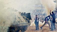 Пропалестинские демонстранты вблизи израильского бронетранспортера во врмя митинга в городе Рамалла на Западном берегу. 27 декабря 2001 года