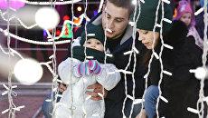 Семья среди новогодних композиций на площади Ленина в Симферополе