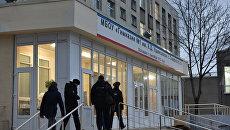 Сотрудники правоохранительных органов заходят в здание гимназии №1 им. К. Д. Ушинского в Симферополе после инцидента со стрельбой