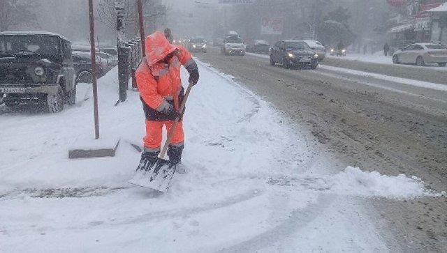 Дворник расчищает обочины дорог от снега в Симферополе. 1 марта 2018