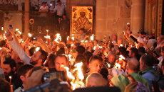 Верующие зажигали свечи и факелы от Благодатного огня в Иерусалиме